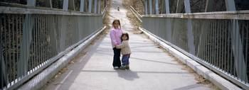 Two little girls standing on a bridge