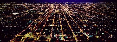 Aerial view of buildings in a city lit up at nigh