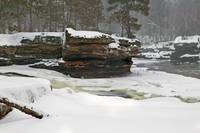 Snow-covered cliffs along misty Kettle River
