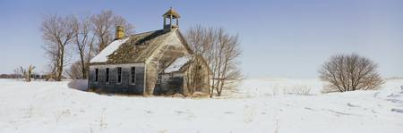 Abandoned schoolhouse on a snow-covered landscape