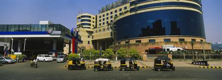 Autorickshaws in front of a commercial building