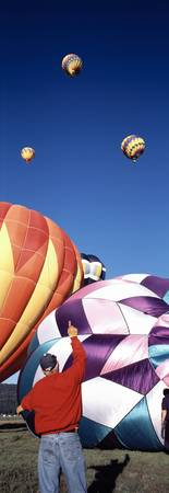 Rear view of a man pointing at hot air balloons f