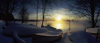 Snow covered boats at the riverside