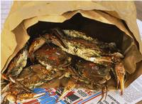 Close-up of steamed crabs in a paper bag