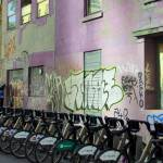 """Rental Bicycles Parked beside Colorful Wall Painti"" by AndreHugosPlace"