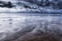 Wet sand, sea and storm clouds
