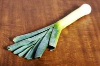 Green fresh leek and its slices on cutting board.