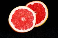 Fresh grapefruit divided into two pieces. On black