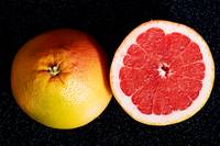 Fresh grapefruit divided into two pieces on black