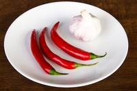 Red chili peppers and garlic on plate