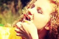 Teen girl eating fresh woodland strawberry outdoor
