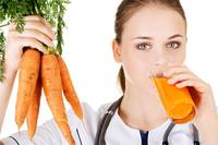 Female doctor holding healthy carrots and juice. I