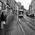"""Man Waiting for Augsburg Tram"" by robertmeyerslussier"