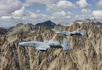 Two A-10 Thunderbolts fly over the mountains in Ce