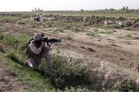 A soldier scans the distance with his rifles scope