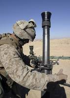 An 81mm mortarman adjusts the mortar sights during