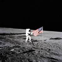 Apollo astronaut stands beside the United States f