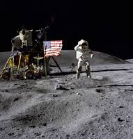 An astronaut stands next to the American flag duri