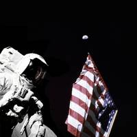 Astronaut stands next to the American flag during