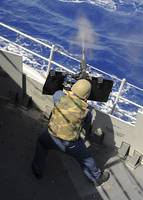 Gunners Mate firing a machine gun aboard the guide