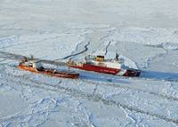 USCG Healy breaks ice around a Russian-flagged tan