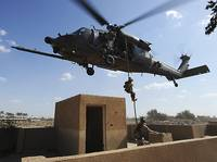 A US Air Force Pararescuemen fast ropes from an HH