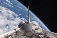 Space Shuttle Discovery backdropped by Earth