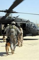 Military working dog handlers board a helicopter