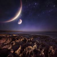 Rising planets hover over ocean and rocky shore ag