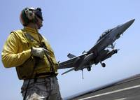 An officer observes an F/A18F Super Hornet prepare