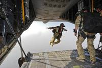 A U.S. Air Force pararescueman jumps out of an HC-