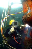 US Navy Diver welds a repair patch on the submerge