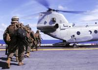 Marines board a CH 46E Sea Knight helicopter aboar