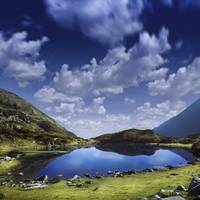 Blue lake in the Pirin Mountains over tranquil clo