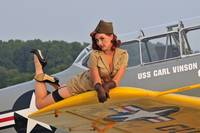 1940's style pin-up girl lying on a T-6 Texan tra