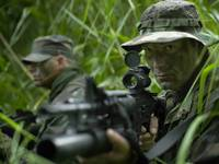 U.S. Special Forces soldiers patrol through tall g