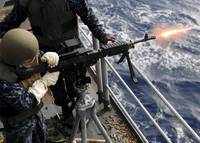 U.S. Navy Airman fires an M 240B machine gun aboar