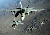 Four U.S. Navy F/A 18 Hornet aircraft fly over mou