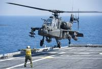 An Army AH-64D Apache helicopter prepares to land
