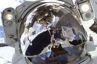 Astronaut uses a digital still camera to take a se