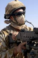 A British Army soldier mans a machine gun mounted