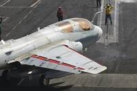 An EA-6B Prowler is guided onto a catapult aboard