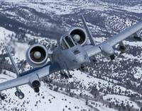 An A-10C Thunderbolt flies over the snowy Idaho co