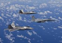 An F-15 Eagle and two F-22 Raptors fly in formatio