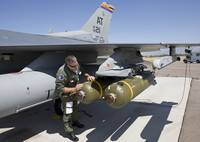 An F-16 pilot conducts a preflight check on a weap