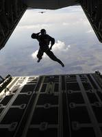 A paratrooper salutes as he jumps out of a C-130J