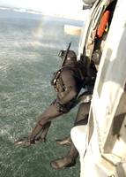 A search and rescue swimmer student jumps from a M