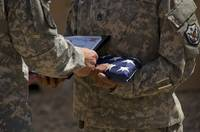 A soldier is presented the American Flag and certi