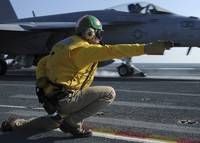 A shooter signals the launch of an F/A-18 Super Ho