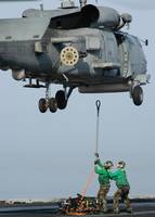 Airmen assist each other as they hook a sling to a